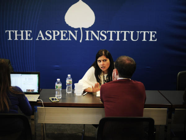 ElsaMarie D'Silva, an Aspen fellow from India who focuses on gender-based violence and harassment, speaks with a reporter during the speed-dating session.