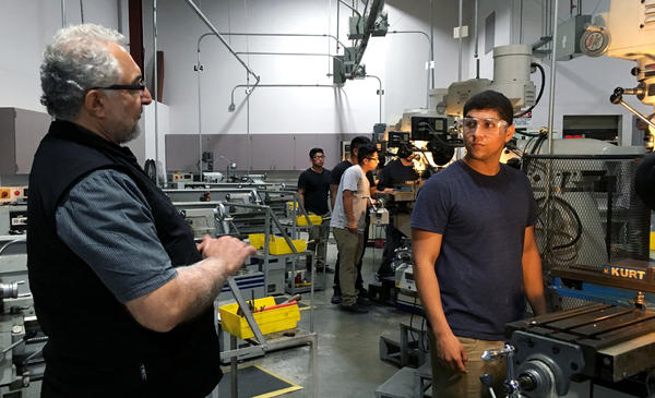 Professor Philip Yaghmai (left) talks to Ismael Becerra, 18, in the lab at El Camino Community College's Compton campus. Students translate machining theory into practice on vertical mills, CNC machines and other heavy equipment used in aerospace fastener manufacturing.