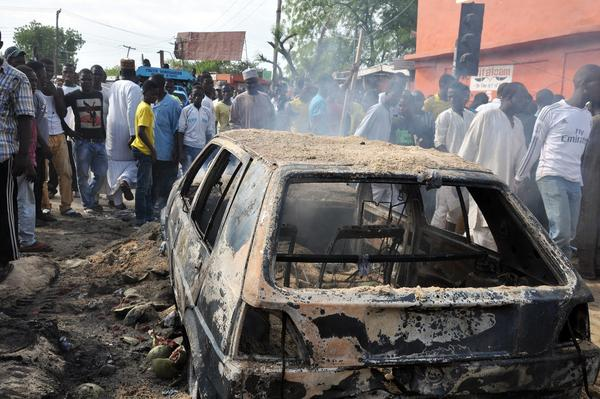 People gather to look at a burnt car following a bomb explosion that rocked a roundabout near the crowded Monday Market in Maiduguri, Nigeria, on July 1, 2014. The city has been repeatedly hit by Boko Haram terrorists. A recent report found that in 2014, the group was responsible for more known deaths from terrorism than any other organization.