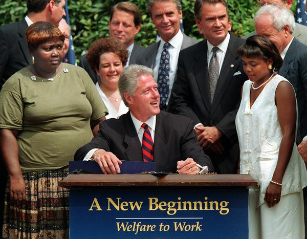 President Bill Clinton prepares to sign legislation in 1996 that overhauled America's welfare system — and had a profound effect on the collection of child support.