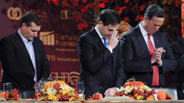 Republican U.S. presidential candidates Ted Cruz, Marco Rubio and Rick Santorum pray at the Presidential Family Forum in Des Moines, Iowa, November 20, 2015. The question of how to treat Syrian refugees has evoked different reactions in political evangelicals.