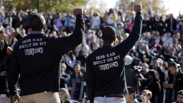 Members of the black student protest group Concerned Student 1950 raise their arms during a rally at Mizzou. Protests like this are making high schoolers look twice at where they want to study and the culture of racism on campus.