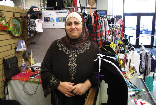 """Nadeen Yousef in her booth, Macrame by Nadeen, at the West Side Bazaar, in Buffalo, N.Y. Yousef moved to Buffalo from Iraq in 2014. """"We are like family here — family from different countries,"""" she says."""