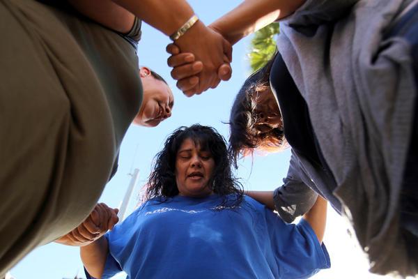 Marie Cabrera, Sonya Gonzalez and Christine Duran, all of San Bernardino, pray after the shooting.