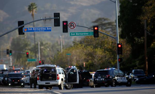 Police draw guns on San Bernardino Avenue while chasing suspects in an SUV. Later, police said alleged shooters Syed Farook, 28, and Tashfeen Malik, 27,  were killed in a shootout with police.