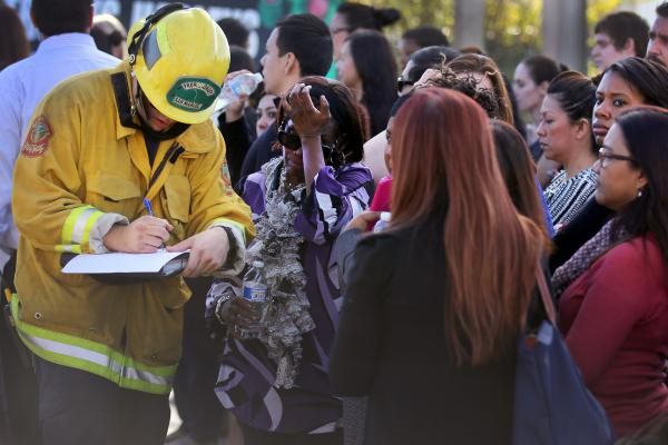A member of the San Manuel Fire Department takes the names of people being evacuated after the shooting.