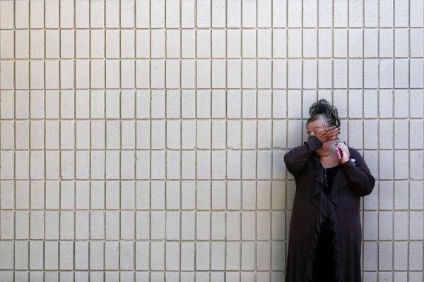 A woman wipes her tears at a community center where family members gathered to pick up survivors.