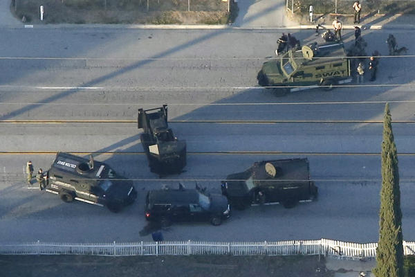 An aerial photo shows police vehicles surrounding and searching a bullet-ridden SUV in San Bernardino.
