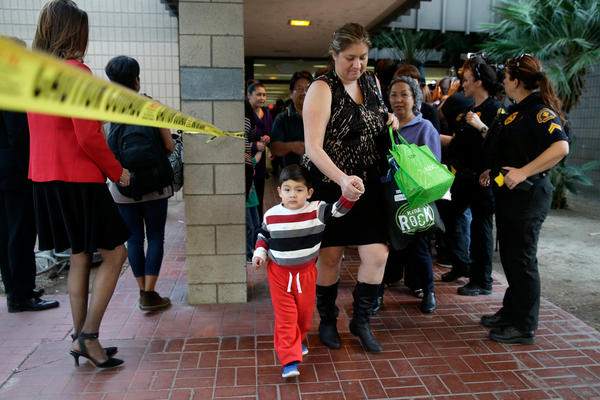 People exit a community center to be reunited with friends and family after a shooting that killed multiple people at a social services center.