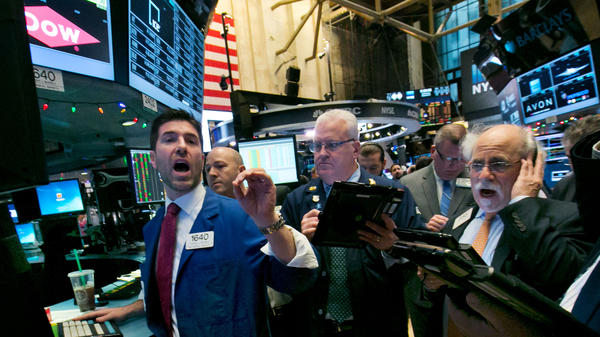 Specialist Thomas McArdle (left) works with traders at the post that handles Dow Chemical on the floor of the New York Stock Exchange. If a proposed merger goes through, Dow's and DuPont's respective shareholders would own about half of the new entity.
