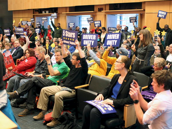 Supporters cheer during a meeting Monday when the Seattle City Council voted to approve a measure that would allow ride-sharing drivers for Uber and other ride services to unionize.