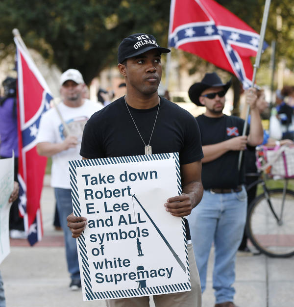 People demonstrate for and against the Confederate monuments in front of City Hall this month.