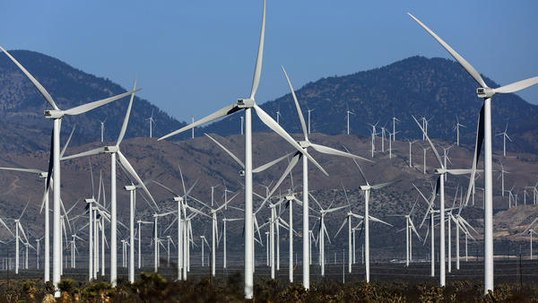 Wind turbines dot the landscape in Mojave, Calif. The recent extension of federal tax credits is expected to give the wind and solar energy industries a big boost.