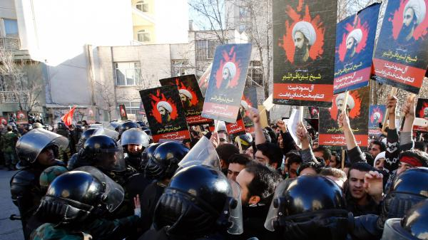 Iranian security forces stand guard as protesters demonstrate outside the Saudi Arabian Embassy in Tehran. The crowd was decrying the execution of Nimr al-Nimr, a prominent Saudi Shiite cleric, by Saudi authorities — an execution that has heightened sectarian tensions in the region.