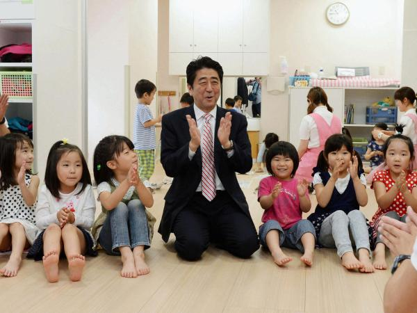 Japan's Prime Minister Shinzo Abe plays with children as he inspects a day care center in Yokohama in 2013. More than 20,000 Japanese children are on wait lists for day care.