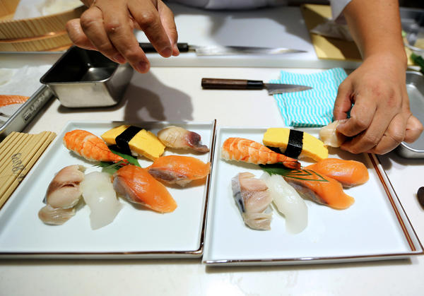 A sushi chef prepares a dish during the Global Sushi Challenge competition in Tokyo in September. Japan's new program will certify Japanese restaurants outside of the country that meet the standards of traditional Japanese food, known as <em>washoku.</em>