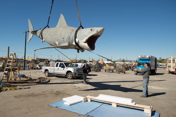 """Workers """"sling"""" the last remaining shark cast from the original <em>Jaws</em> mold and lift it, by crane, to a nearby crate. After spending more than 25 years at a Los Angeles junkyard, """"Bruce"""" is headed for a museum."""