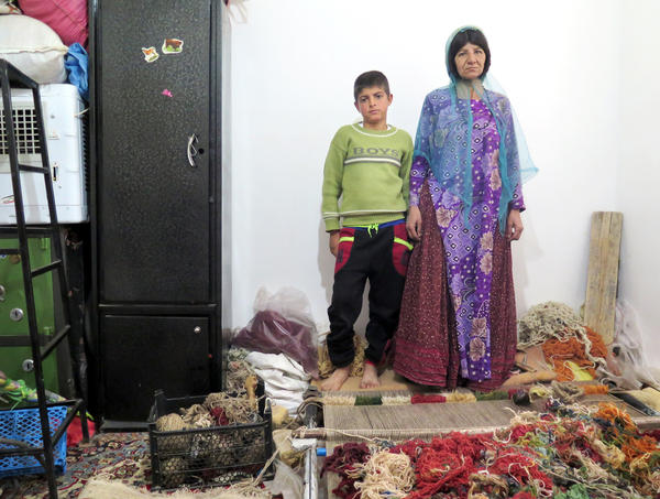 Zarafshan, shown here with her 10-year-old son, earns money by weaving carpets. But it's not enough to support her family of five children.