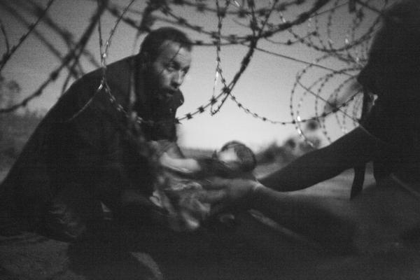 A man passes a baby through a barbed wire fence at the Serbia/Hungary border in Röszke, Hungary, on Aug. 28, 2015.