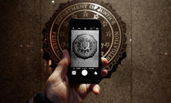 The official seal of the Federal Bureau of Investigation is seen on an iPhone's camera screen outside the J. Edgar Hoover headquarters in Washington, D.C. Apple is facing off with the FBI in court over investigators' request that the tech giant help them circumvent the iPhone's security features.