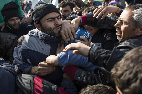Refugees scrabble among each other as they stage a protest Tuesday along the Greek-Macedonia border near Idomeni.