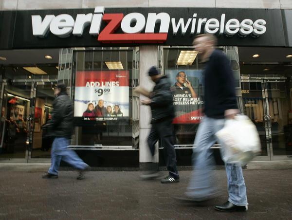 Pedestrians walk past a Verizon Wireless shop.