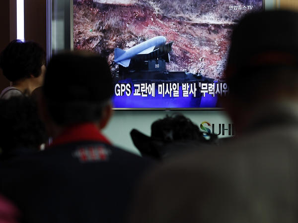 At the Seoul railway station, South Koreans watch a television broadcast reporting North Korea's surface-to-air missile launch on April 1.