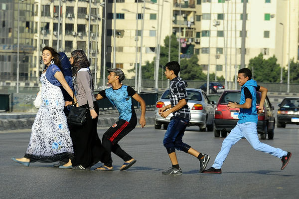 An Egyptian youth, trailed by his friends, gropes a woman as she crosses a Cairo street.