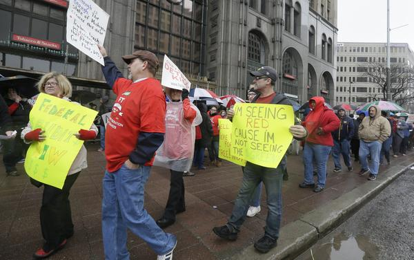 Teachers march outside the district headquarters on Monday in Detroit.
