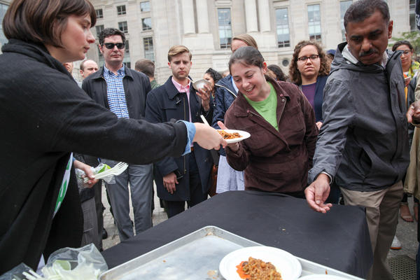 A volunteer hands out plates of paella.