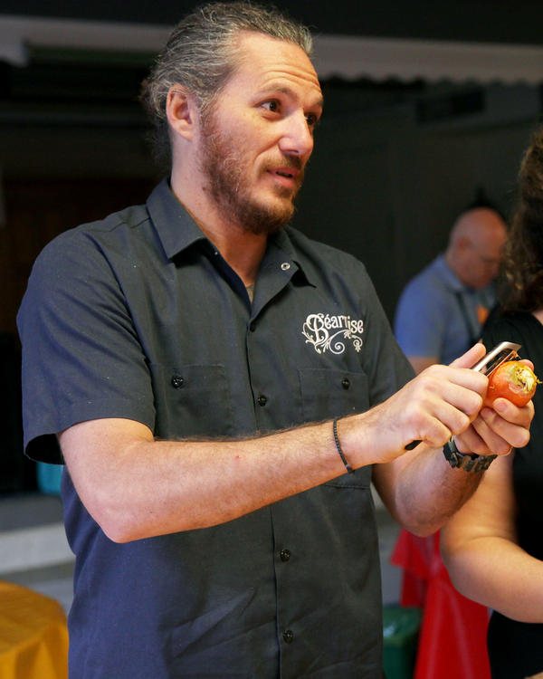 Celebrity chef and restaurateur Spike Mendelsohn, along with dozens of other volunteers, peels carrots on Tuesday to be used for Wednesday's feast.