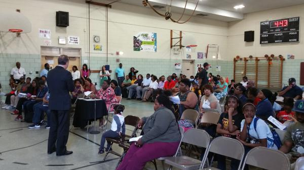 Angry parents attend a community meeting in the Tanner Elementary School gym, where school and city officials listen to their concerns.