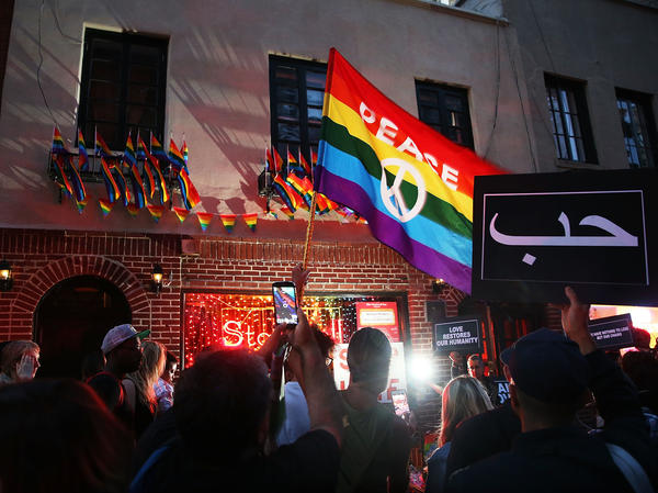 Mourners gather outside of the iconic New York City gay and lesbian bar the Stonewall Inn to light candles, lay flowers and grieve for those killed in Orlando last evening on June 12, 2016.
