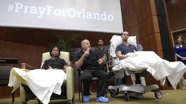 Shooting victims Patience Carter of Philadelphia (left) and Angel Santiago (right) listen as Dr. Brian Vickaryous speaks during a news conference Tuesday regarding the treatment of victims of the Pulse nightclub shooting in Orlando, Fla.
