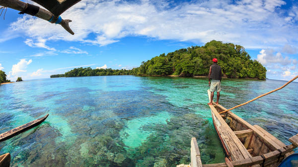 A fisherman surveys the shallow coral reef near a small island in Papua New Guinea. Some of the reefs around these islands are surprisingly healthy as a result of active fishery management by local people.
