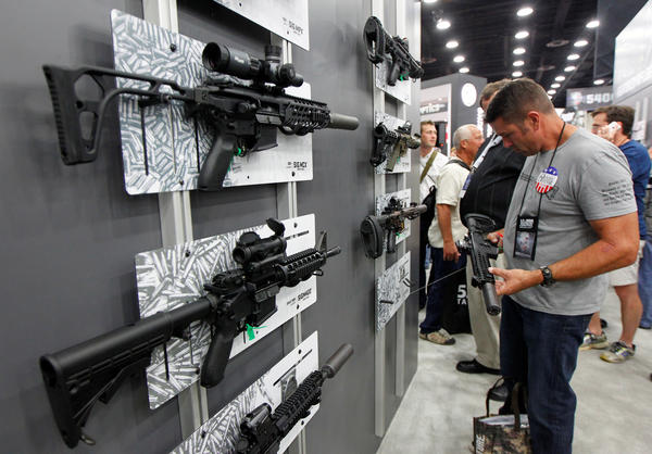 A Sig Sauer MCX rifle can be seen on display at the top left of this photo as NRA gun enthusiasts view the Sig Sauer display at the National Rifle Association's annual meetings & exhibits show in Louisville, Ky., in May.