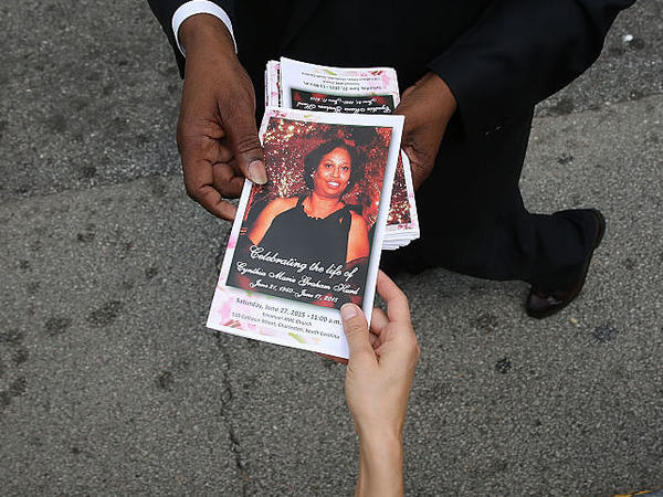 A program with a cover photograph of Cynthia Hurd, 54, is handed out before her funeral at the Emanuel African Methodist Episcopal Church where she was killed along with eight others in a mass shooting at the church on June 27, 2015 in Charleston, South Carolina.