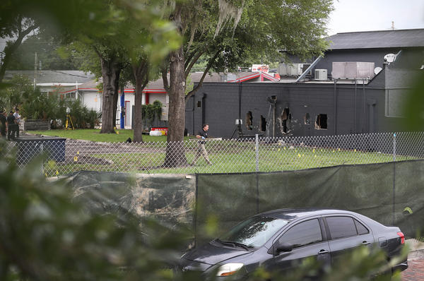 FBI agents investigate near the damaged rear wall of the Pulse club, where police used explosives and an armored vehicle to break through the cinder block.