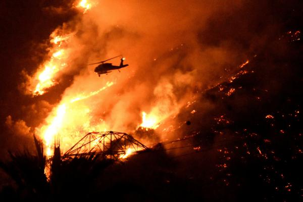 A Los Angeles County fire helicopter makes a night drop while battling the Fish Fire above Azusa, Calif., on Monday.