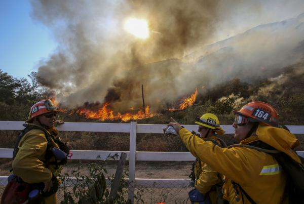 Firefighters watch a blaze in Azusa on Monday. New wildfires erupted Monday near Los Angeles and chased people from their suburban homes as an intense heat wave stretching from the West Coast to New Mexico blistered the region.