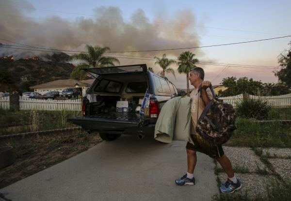 A man evacuates his home as a wildfire burns along a hillside in Duarte on Monday. Police in the city of Azusa and parts of Duarte ordered hundreds of homes evacuated. Others were under voluntary evacuations.