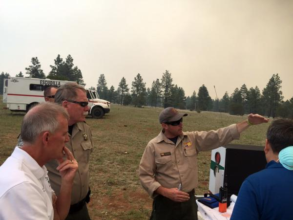 Navajo County Sheriff KC Clark (second from left) attends a wildfire briefing last week from a U.S. Forest Service official at Fort Apache Indian Reservation, Ariz.