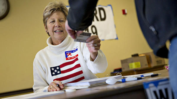 A poll worker checks the identification of a resident at a polling location during the Wisconsin presidential primary on April 5.