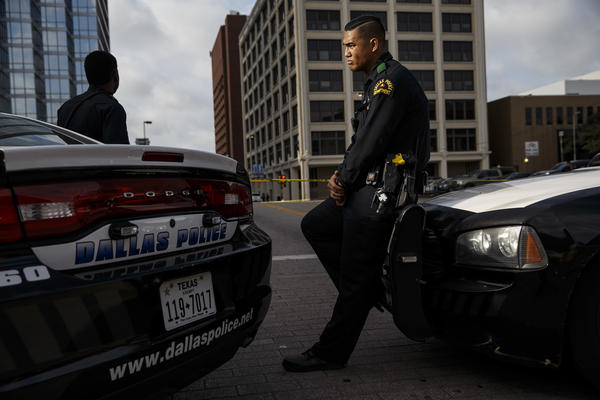 Dallas police officers stand guard at a roadblock to the crime scene at El Centro College, where a sniper unleashed a barrage of bullets, killing five police officers and wounding seven others.