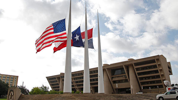 Flags fly at half-staff on Friday at Dallas City Hall, following the fatal shootings of five police officers the night before.