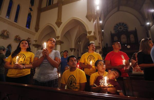 "Worshipers participate in a ""United To Heal Prayer Vigil"" at Cathedral Guadalupe in Dallas on Friday, in honor of the police officers who were slain on Thursday."