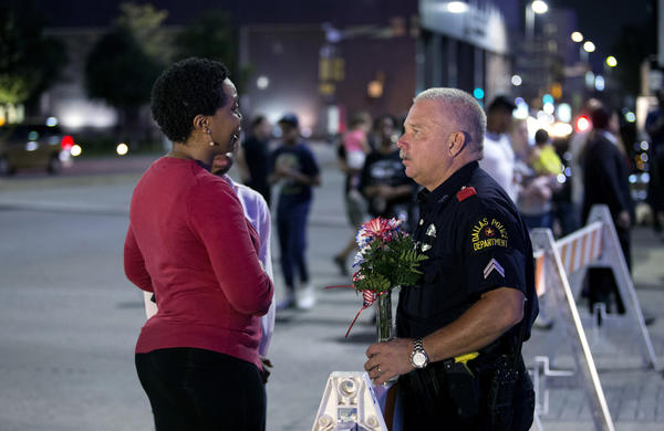 A woman speaks with an officer at a vigil outside Dallas police headquarters in Dallas on Friday.