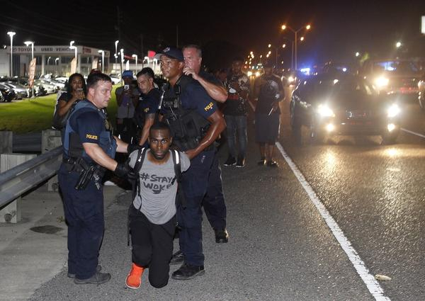 Police arrest activist DeRay Mckesson on Saturday, during a protest along Airline Highway, a major road that passes in front of the Baton Rouge Police Department headquarters in Baton Rouge, La.