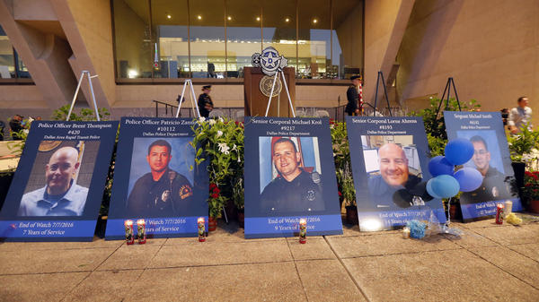 Portraits of the five murdered Dallas police officers sit in front of city hall.