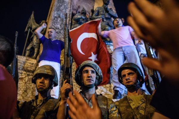 Turkish solders at Taksim square in Istanbul are surrounded by pro-government demonstrators early Saturday.